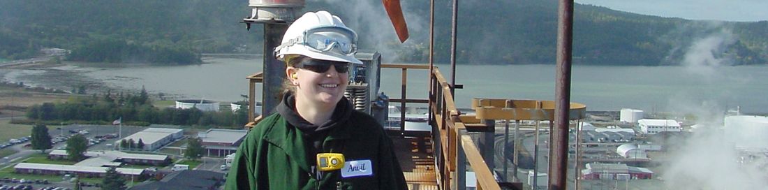 Woman engineer smiling standing on top of refinery equipment walkway